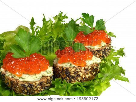 Sandwiches with red caviar, made from black baguette sprinkled with grains of cereals and poppy, lie on green leaves of salad