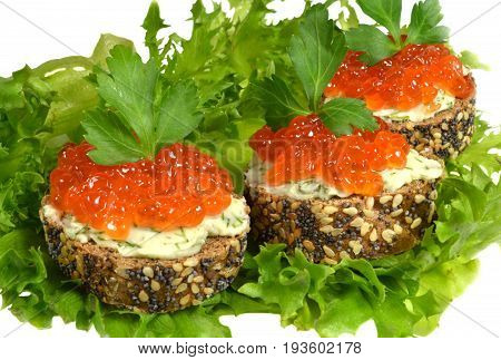 Three small sandwich with red caviar, made of black baguette, sprinkled with grains of cereals and poppy, lie on green lettuce leaves