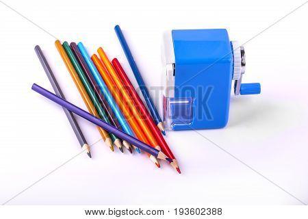 Color pencils and mechanical sharpener on white background