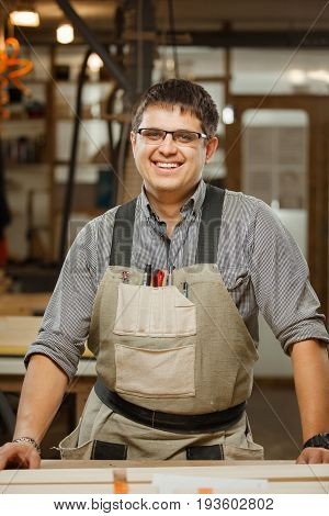 Smiling professional carpenter in gasses and uniform at workshop. Handsome mature craftsman at work. designer or constructor of wooden materials