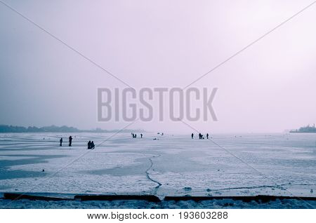Winter on the lake. Frozen lake. People enjoy on frozen lake on cold misty day. Palic lake, Serbia.