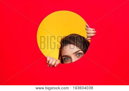 Young woman looking with precaution out of circle in red paper on yellow background.