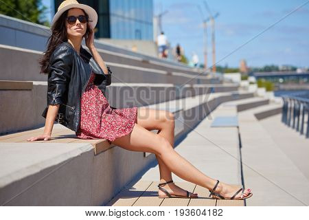 Expressive attentive look woman in grey  hat. Urban port river background. Natural light