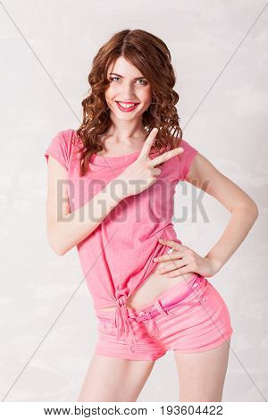 girl pinup-style in a pink dress shows 2 fingers