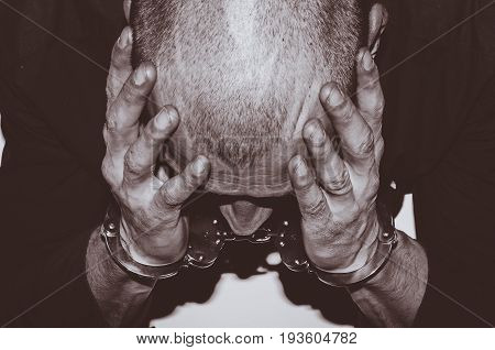 Arrested criminal. Arrested criminal with handcuffs on his hands sitting at the white table in  police station. Crime concept.