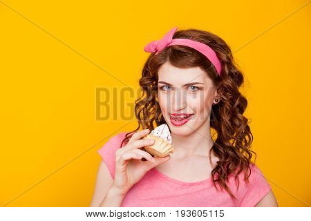 girl in pink dress pinup-style eats cake with cream 1