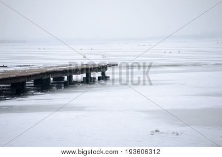 Pier. Wooden pier on frozen lake on foggy winter morning. Palic lake, Serbia.