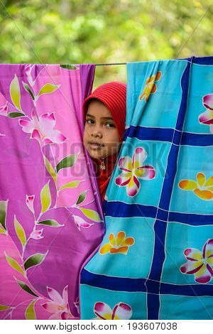 KRABI THAILAND - MAY 2 2015: Lovely Muslim girl hiding back of dried Batik fabric looking to visitor in Lanta island of Krabi Thailand
