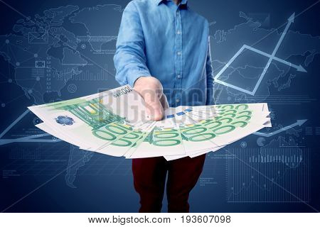 Young businessman holding large amount of bills with blue charts in the background