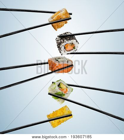 Sushi pieces placed between chopsticks, separated on soft background. Popular sushi food. Very high resolution image