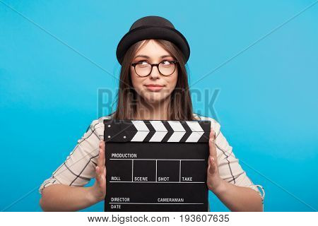Young stylish girl in hat holding clapboard on blue background.