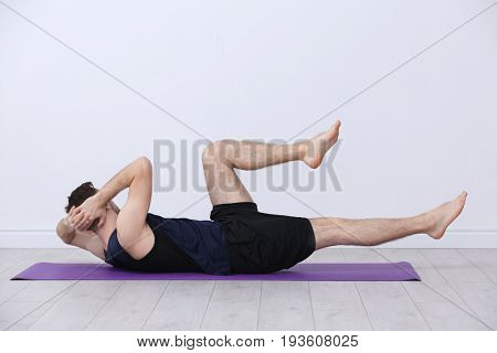 Young man doing bicycle crunch exercise on white wall background