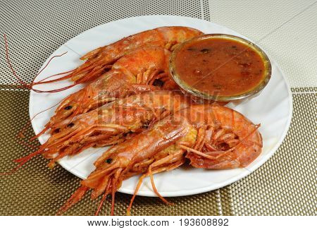 Four langoustines, stewed in saute sauce, on white plate