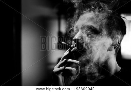 Cigarette addict. Person smoking cigarette. Black and white. Hard contrast. With film grain. Cigarette smoke. Addiction.