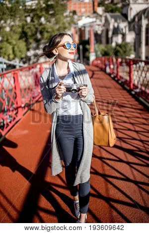 Stylish woman with photocamera enjoying morning city standing on the famous red footbridge in Lyon, France