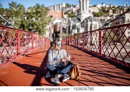 Young stylish busineswoman sitting with phone and bag on the red footbridge in Lyon, France