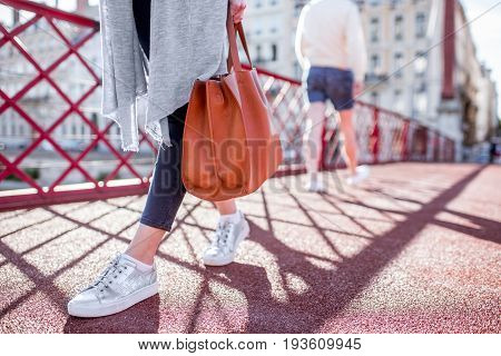 Businesswoman walking with bag on the red footbridge. Close-up view on the legs
