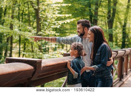 Young Smiling Interracial Family Standing On Wooden Bridge, While Father Pointing Somewhere Into The