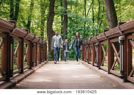 Young Interracial Family Holding Hands And Walking Through The Wooden Bridge In Forest