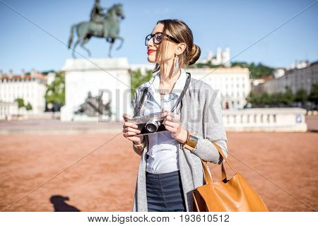 Young woman with photocamera standing on the famous Bellecour square with Louis king statue traveling in Lyon city in France