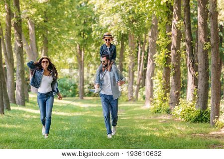Young Interracial Family Walking In Forest, Father Carrying His Daughter On Shoulders