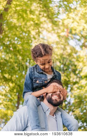 Happy father carrying adorable little daughter on shoulders while walking in park