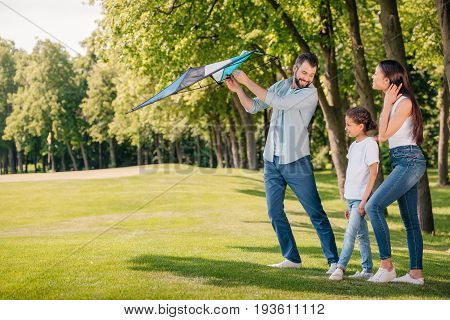 Father Helping Daughter Launching Kite While Spending Time Together In Park
