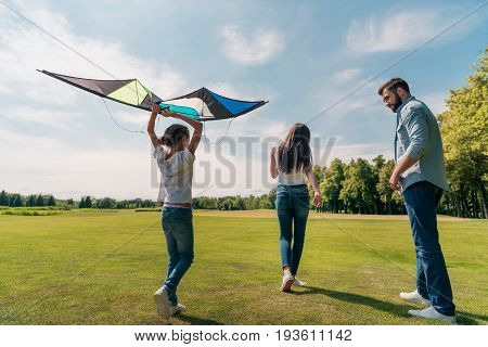 Back View Of Girl Holding Kite With Parents Walking Near By In Meadow