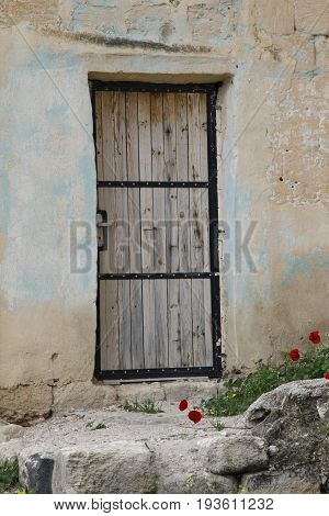 Shot Showing An old wooden door light beige color and small red flowers and some stones in jordan