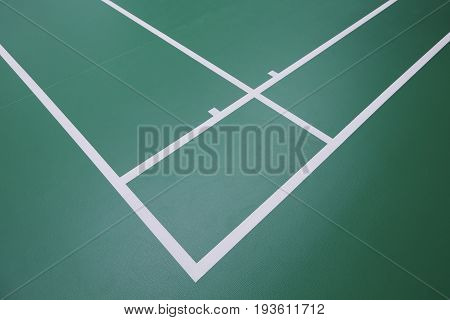 Empty green colour corner badminton court for training and tournament.