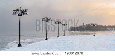 Snowy Embankment Along The Misty River With Lanterns At The Foggy Sunrise - Winter Landscape.