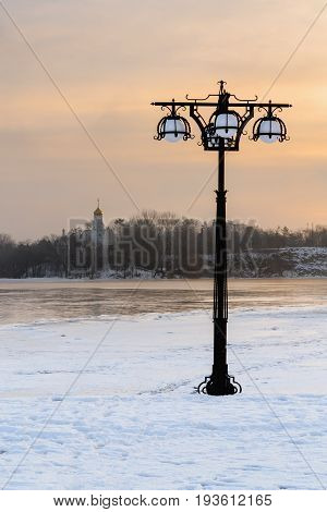 Snowy Embankment Along The Misty River With Lanterns At The Foggy Sunrise - Winter Landscape. Iii