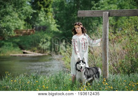 Portrait of a beautiful girl in Slavic clothes. Young woman with a Siberian husky dog. Summertime