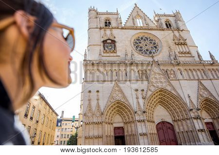 Woman looking at the famous saint John cathedral in Lyon city in France