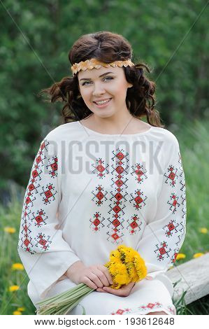 Portrait of a beautiful girl in Slavic clothes. Smiling woman with a bouquet of dandelions sitting on a wooden bench. Summertime