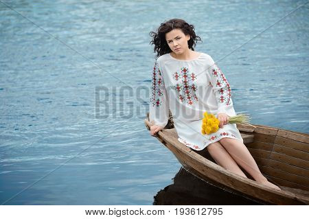Portrait of a beautiful girl in Slavic clothes. Young woman with a bouquet of dandelions is sitting in a wooden boat. Summertime