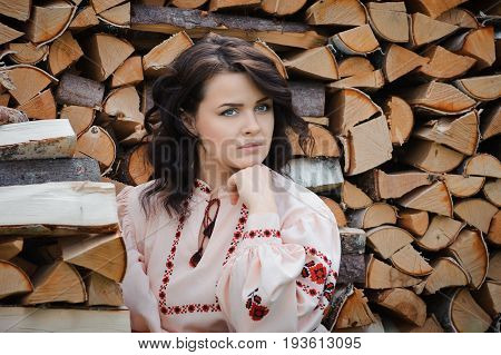 Portrait of a beautiful girl in Slavic clothes on the background of a woodpile. Summertime
