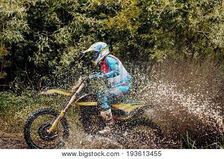 Kyshtym Russia - June 18 2017: motorcycle rider crosses puddle splashes of water and dirt during Ural Cup in Enduro