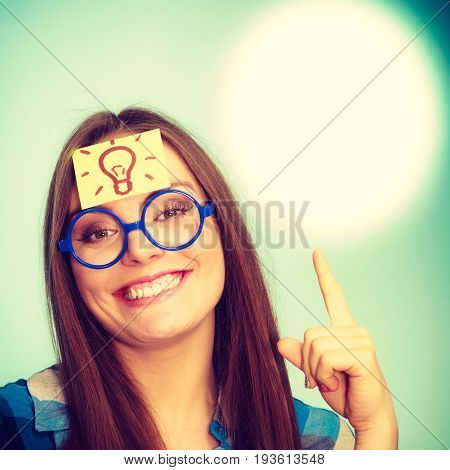 Woman confused thinking seeks a solution paper card with light idea bulb on her head. Excited girl with many ideas celebrates success. Eureka creativity concept on green