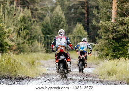 Kyshtym Russia - June 18 2017: back two motocross enduro athlete puddle of dirt and water in Ural Cup Enduro