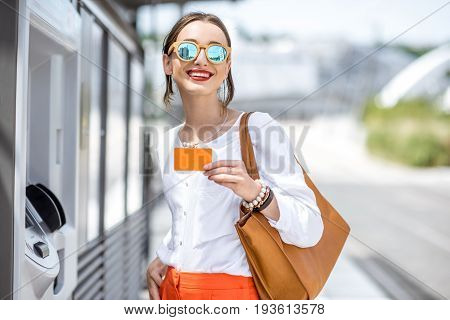 Young woman buying a ticket for public transport at the automatic machine or withdrawing money with a card standing outdoors at the modern city