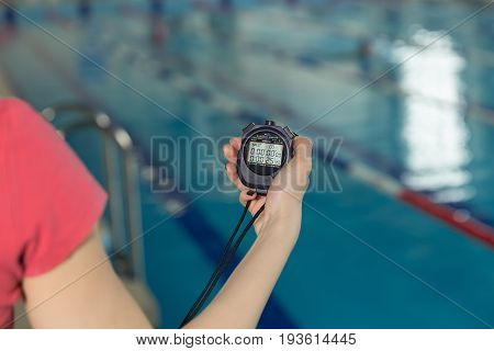 Close-up Of Coach Hand Holding Stopwatch At Poolside