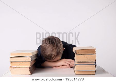 A child of primary school age do homework. The boy does his homework at his desk at home. Pupil has been bored on the lesson. Boy fell asleep during homework. Lovely first grader.