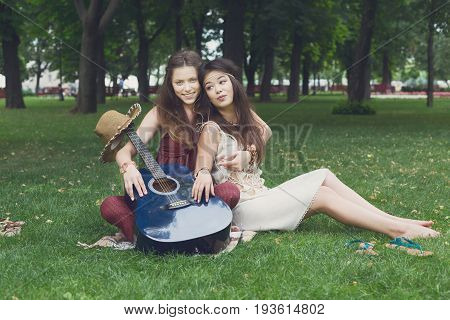 Fancy girls musicians have picnic in park on grass. Modern hippie boho style
