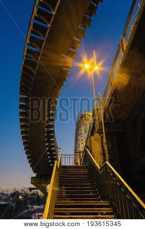 Deserted pedestrian bridge at night in the lighting of street lamps in the city of Dnepropetrovsk, Ukraine