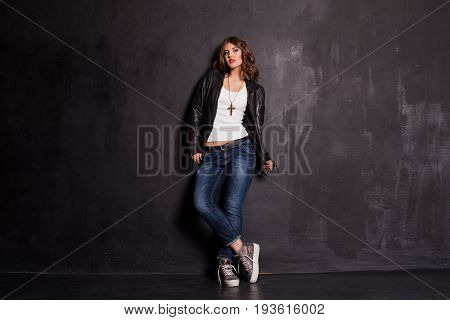 girl in fancy leather jacket pitchman style on a black background