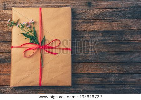 Gift in wrapping paper tied with red ribbon and daisy flower on wooden retro grunge background with space for text top view close-up toning photo