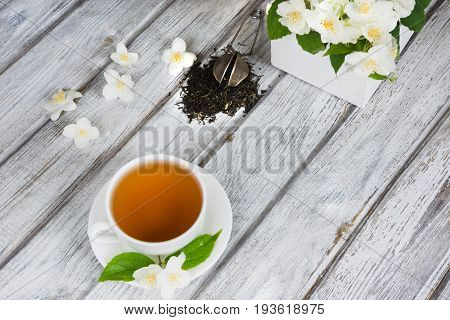 Jasmine dry green tea leaves with fresh jasmine flowers and white cup of green tea on wooden board. Top view.