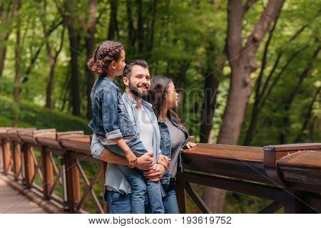Young happy interracial family standing on wooden bridge while father holding his daughter in arms