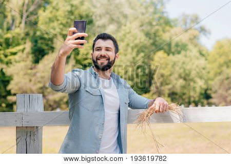 Smiling Bearded Man Standing At Wooden Fence And Taking Selfie On Smartphone